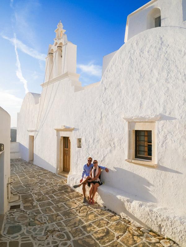 couple sitting against church wall folegandros greece