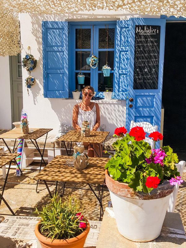 girl sitting at a cafe in folegandros greece