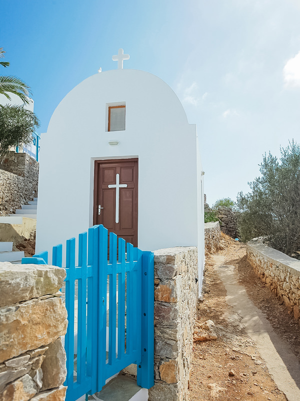 small church with a blue gate in folegandros greece