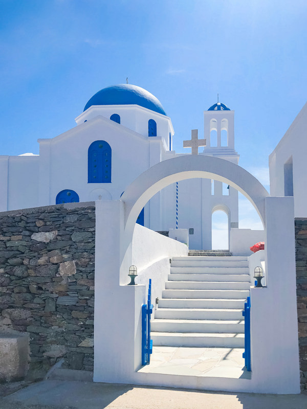 white a blue church with a gate in folegandros greece